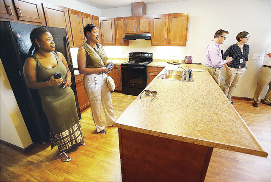 People toured one of the new homes in the Toledo Estates housing complex Tuesday including the new occupant of this three-bedroom house, Demetria Faine, far left. Five houses are now completed in the spot where housing authority apartment units once stood.