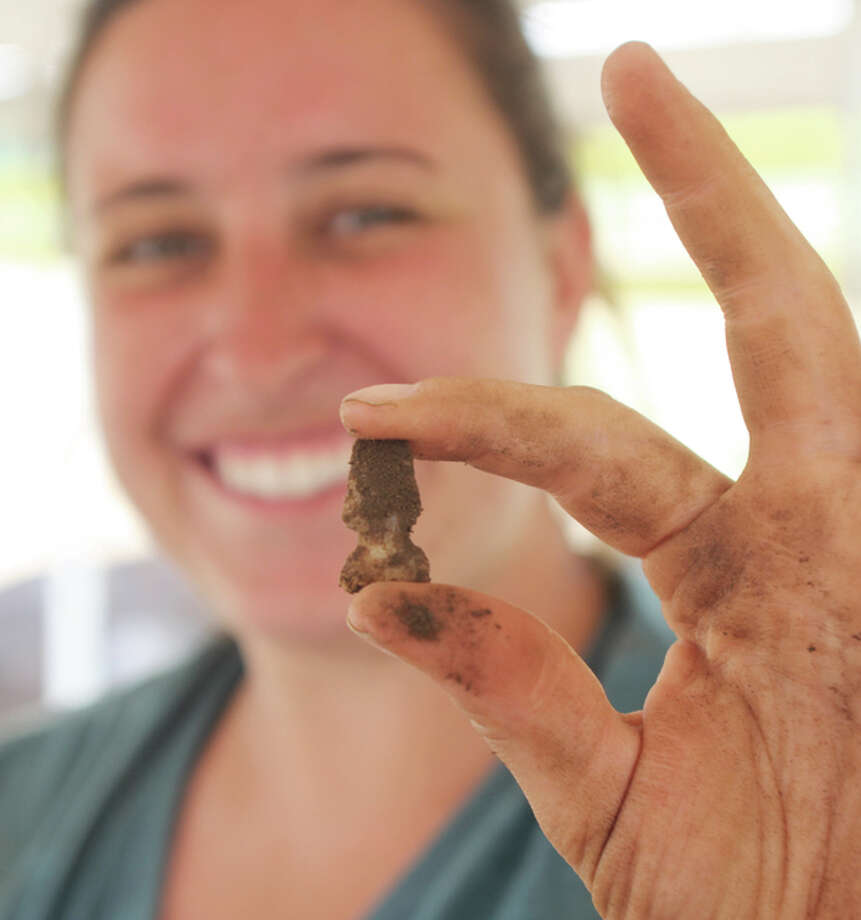 Elizabeth Storey, of Jerseyville, a member of this year's Archaeology Field School at SIUE, holds up a small arrowhead she just found while excavating a pit in the middle of a horseradish field in the southwestern corner of the campus. About a dozen students, assistants and an instructor have been digging at the site for several weeks.