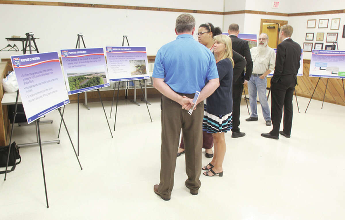 Members of the public talk with Illinois Department of Transportation officials at a public meeting on the replacement of the I-270 Mississippi River bridge, held Thursday at the Sam Wolf Campus of Southwestern Illinois College in Granite City.