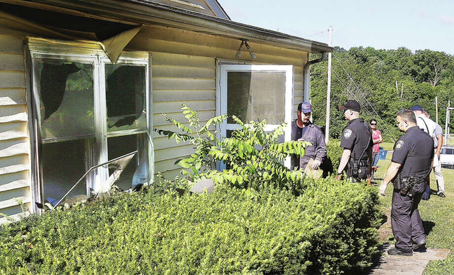 Alton Fire Department investigators and Alton Police enter the house at 3 West 20th Street in Alton Friday after an early morning fire at the residence damaged the house. The cause is undetermined and still under investigation.