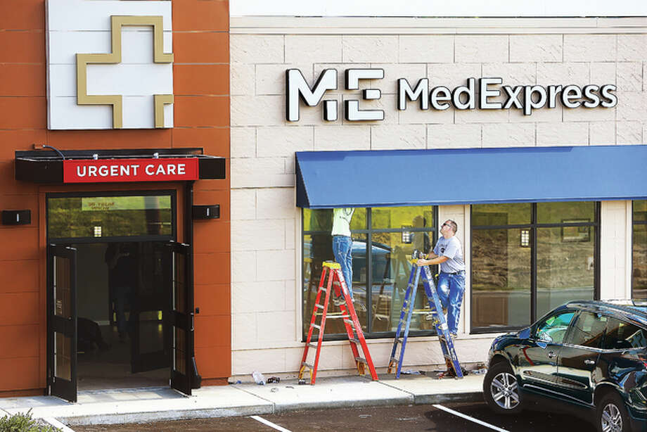 Two men work under the awning of the new MedExpress, which will be opening soon on the Homer Adams Parkway near Buckmaster Lane. The business provides urgent care services to the community as an alternative to a trip to the emergency room for more minor injuries. Photo: John Badman | The Telegraph