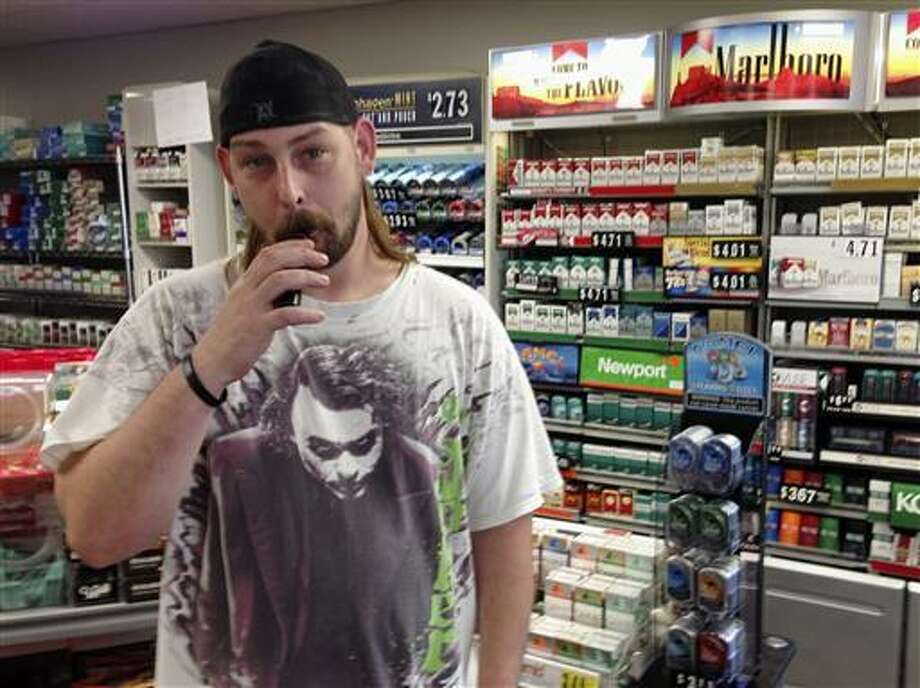 In this June 23 photo, Kenneth Houser takes a puff on an electronic cigarette at the We B Smokin store where he works in Jefferson City, Mo. Houser says he has smoked traditional cigarettes since age 13 but is trying to quit, partly because of the potential for prices to rise under a pair of tobacco tax initiatives proposed for the Missouri ballot.