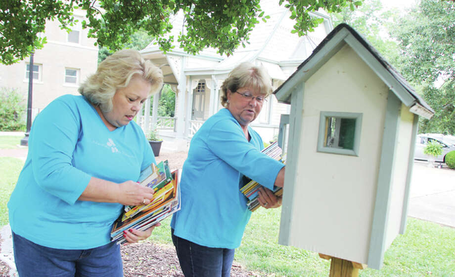 Jan Campbell, left, and Ralona Wittels, members of Phi Tau Omega, a women's sorority, put new books in the Free Little Library at Haskell Park Saturday. The organization has partnered with the Hayner Public Library and Alton School District to set up small libraries, where children can take out books to read, then simply put them back.
