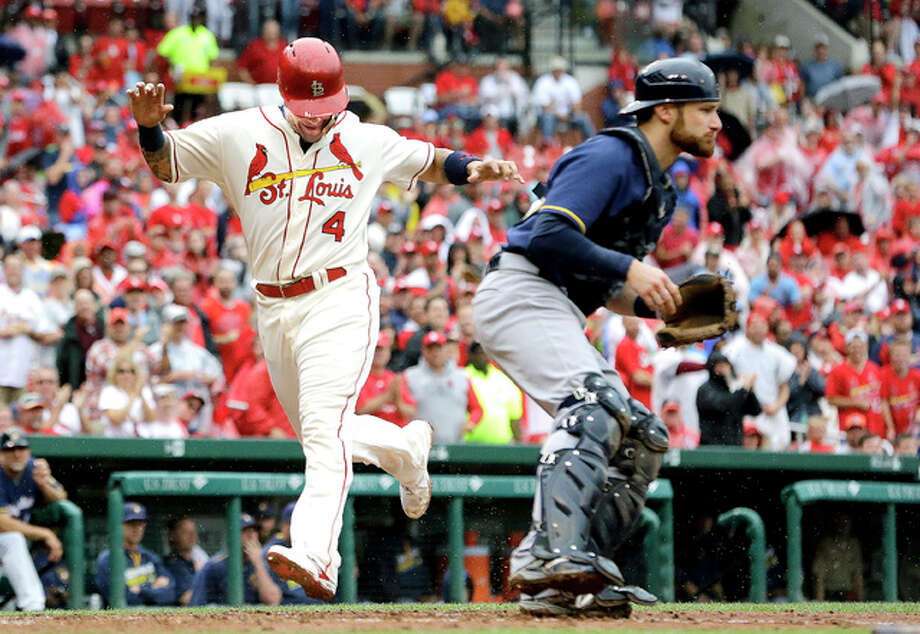 The Cardinals' Yadier Molina, left, scores past Milwaukee Brewers catcher Jonathan Lucroy on a two-run triple by Kolten Wong in the fourth inning of Saturday's 3-0 Cardinals victory. Photo: AP Photo