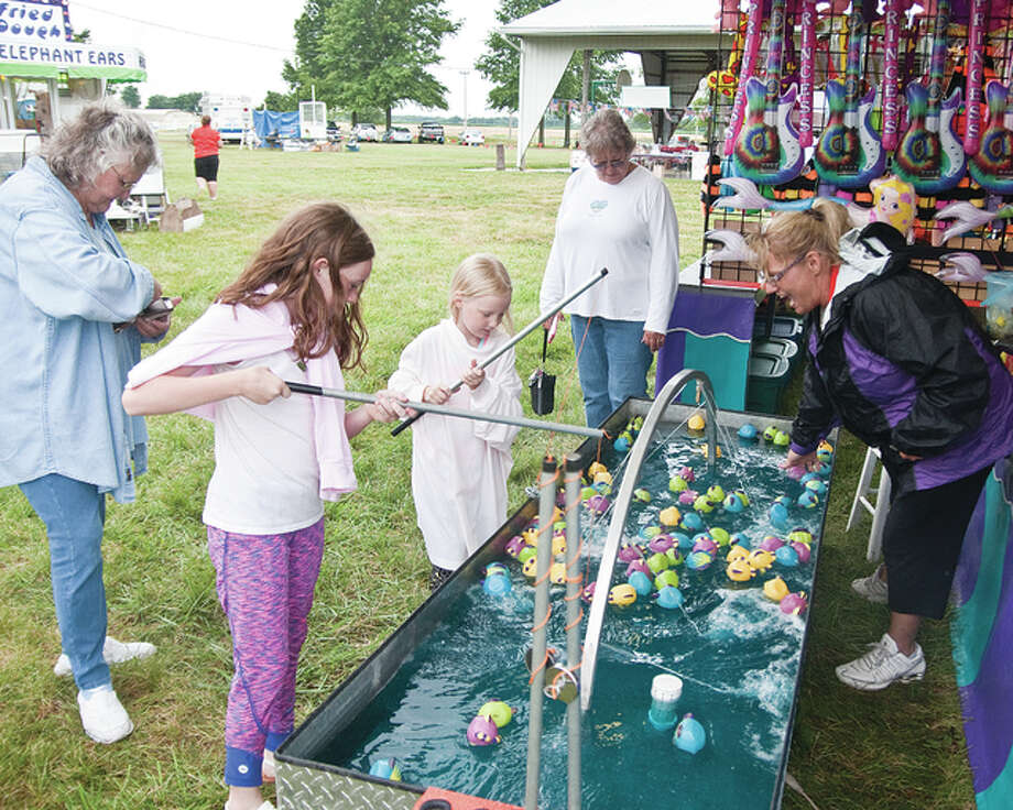 "Nine-year-old Erica Braatz, left, and 6-year-old Erin Braatz attended the Independence Day at the Park event in Brighton on Saturday, trying their luck at catching some fish while ""Fish Till You Win"" operator Markee Richardson looks on."