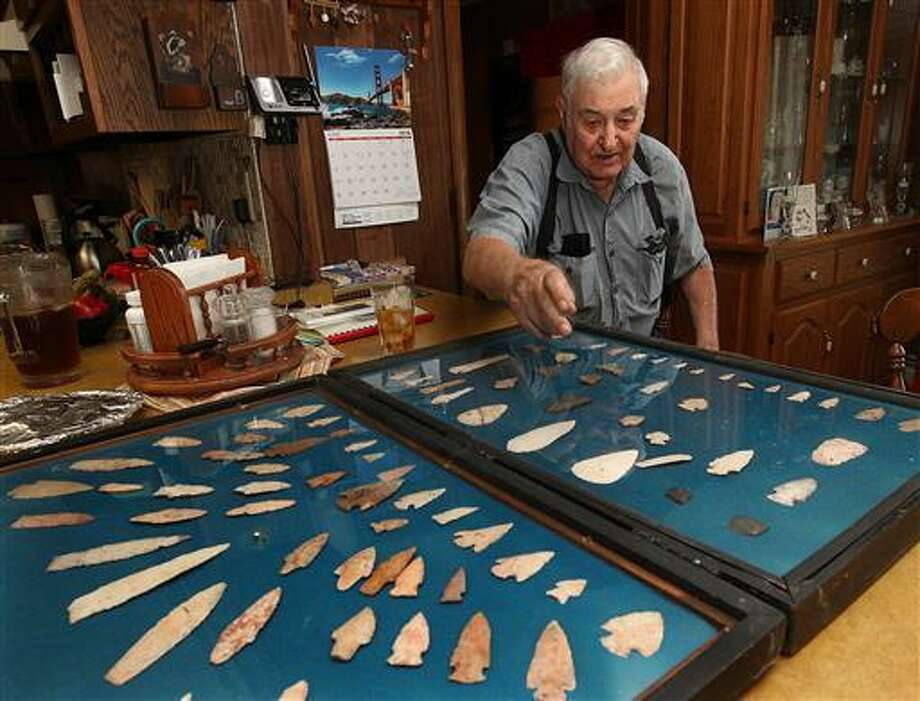 In this June 7 photo, longtime arrowhead collector Eddie Johnson points out various aspects of his collection in his rural Pike County, Ill., home. Johnson has been collecting arrowheads since he was a young boy.