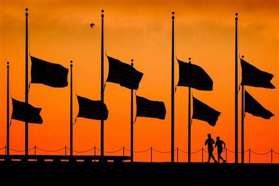 In this June 13, 2016 file photo, flags fly at half-staff around the Washington Monument at daybreak in Washington, by order of President Obama, the day after more than four dozen people were killed in the Orlando, Fla., nightclub shootings. As the nation marks Independence Day on Monday, lowering the flag remains a visible, immediate way to pay tribute in hours of tragedy, but flag buffs have noted that the honor has been extended more widely over time, and they and other Americans have questioned whether the country has lowered the bar on the lowering the flag.