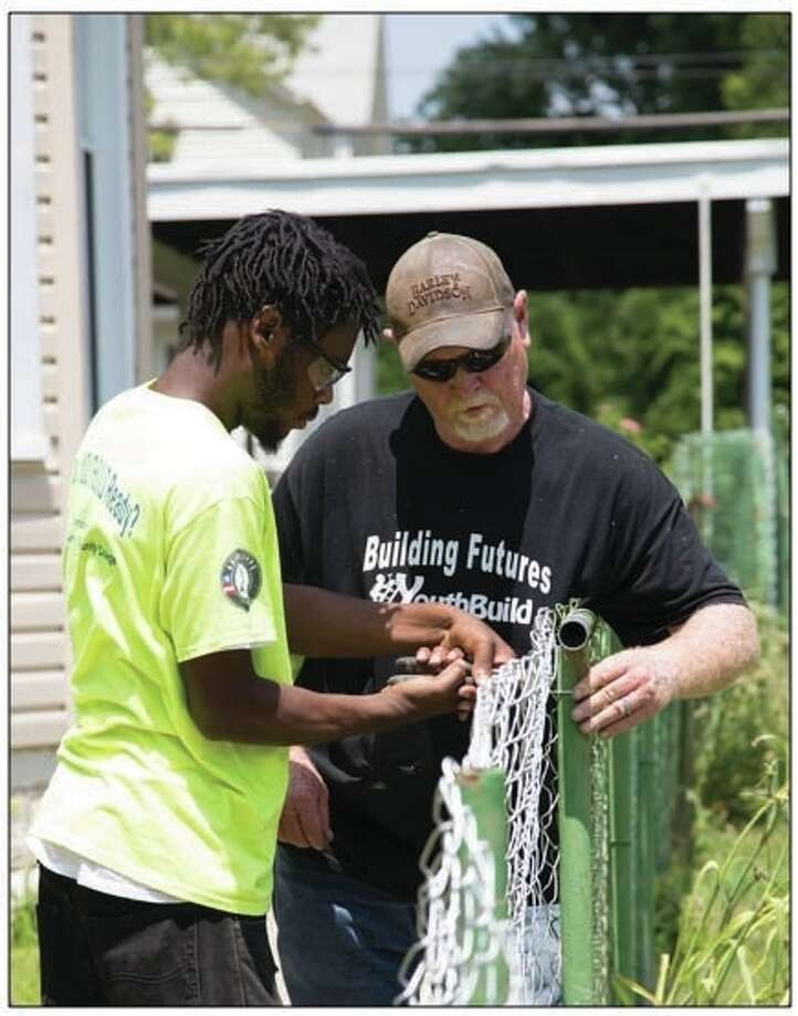 YouthBuild student and recent GED graduate Andre Ewing works on the installation of a new fence with construction trainer Mitch Fletcher, Monday, June 20, as part of the program's Central Avenue Beautification Project. Photo by Laura Inlow, LCCC Media Services Manager|For The Telegraph