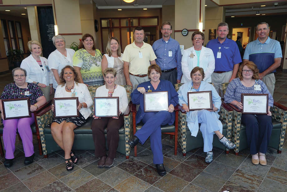 Alton Memorial Hospital managers and senior leaders show off the six Professional Research Consultants awards earned by the hospital in 2015. Front row left to right are Pam Colley of the Transitional Care Unit; Stacey Ballard of Oncology/Medical Imaging; Joellen Corona of the Human Motion Institute; Cindy Bray of the Surgical Care Unit; Angie Henry representing the Cardiac Cath lab; and Heather Bowker of Patient Access; in the back, left to right, are Mary Bayer of Oncology/Twin Rivers MRI; Tammy Merritt of Medical Imaging; Debbie Turpin, vice president of Patient Care Services; Susan Koesterer, vice president of Finance; President Dave Braasch; Dr. Sebastian Rueckert, vice president, chief medical officer; Cathy Storey, regional lab director; Brad Goacher, vice president of Operations; and Rusty Ingram, director of Business Development. Photo: For The Telegraph