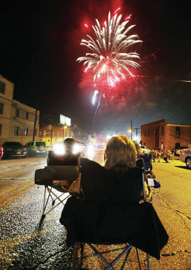 People set up their chairs Sunday night in the middle of Henry Street in Downtown Alton to watch the annual fireworks show. Despite the threat of rain, hundreds turned out in the last minutes to crowd city streets.