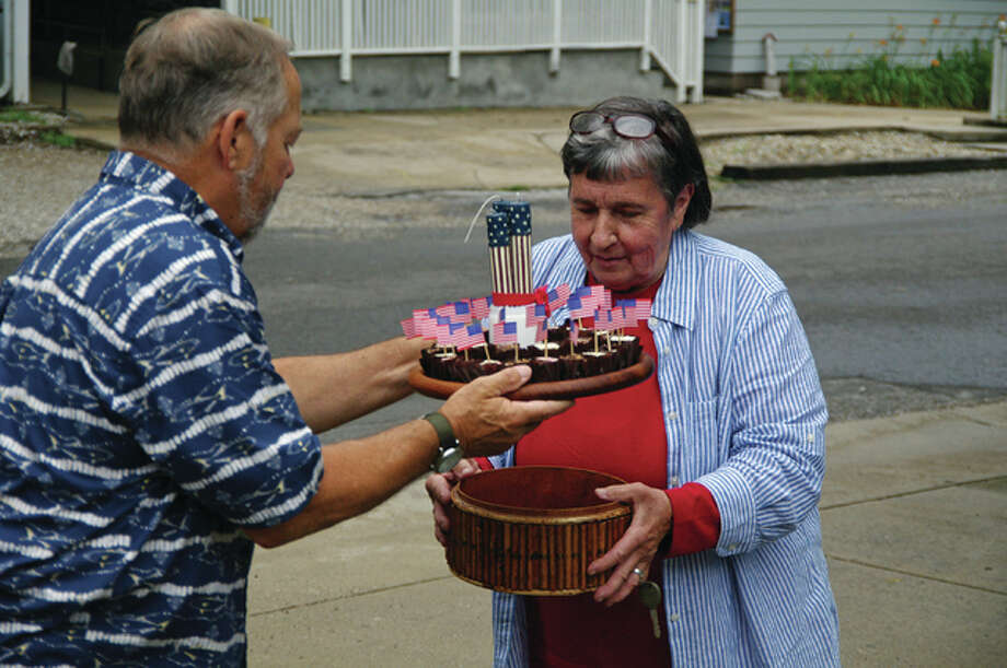 Mike Pitchford helps Sally Menke carry in items for the community potluck following the Fourth of July Parade in Elsah. Photo: David Blanchette|For The Telegraph