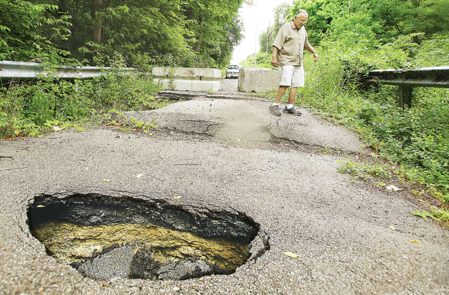 Godfrey Mayor Mike McCormick walks around a sinkhole in the Ingham Lane bridge crossing. The crossing has been closed for two to three years, but it will be fixed in a few weeks' time after the village partnered with a railroad company to help reduce the cost of repairs.