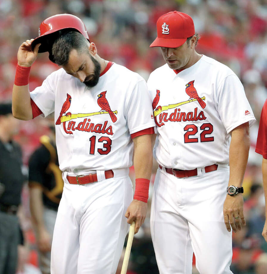 The Cardinals' Matt Carpenter, left, leaves Wednesday night's game alongside manager Mike Matheny. Carpenter was injured while batting in the third inning against the Pirates in St. Louis. Photo: Jeff Roberson | AP Photo