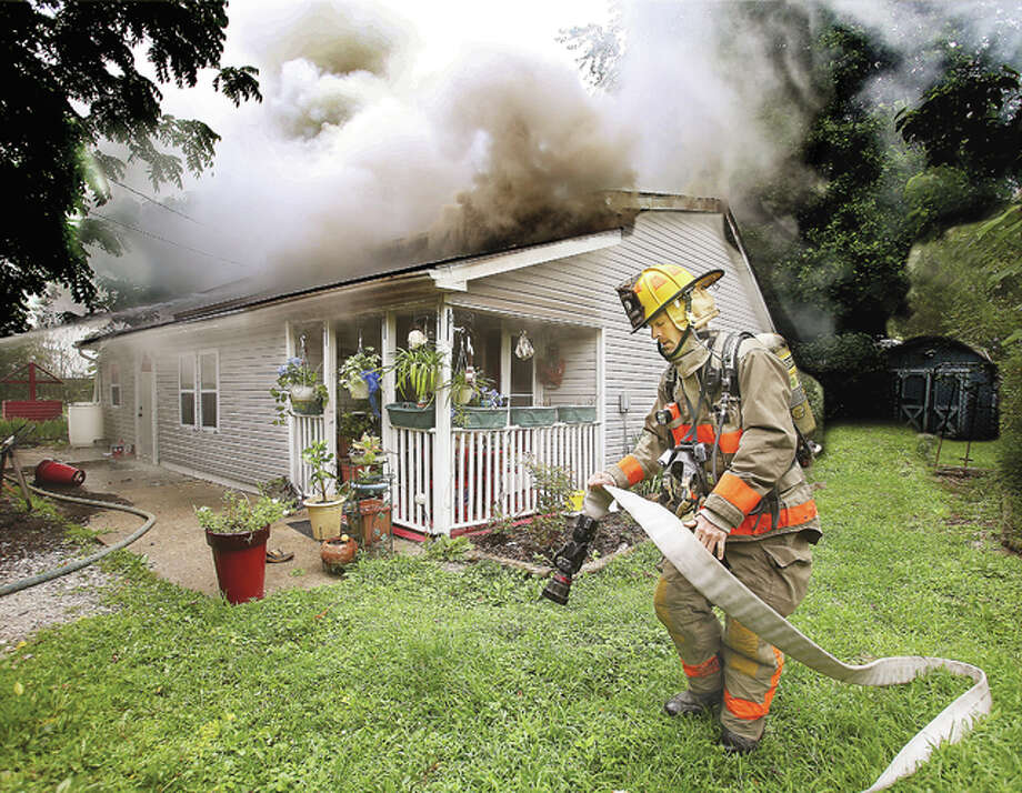A Fosterburg firefighter pulls a two and a half inch hose line into position Thursday as smoke rolls from the roof line of a house in the 4900 block of Columbia Street in Fosterburg. The resident escaped injury but the house was extensively damaged despite the efforts of firefighters from Fosterburg, Godfrey and Brighton.