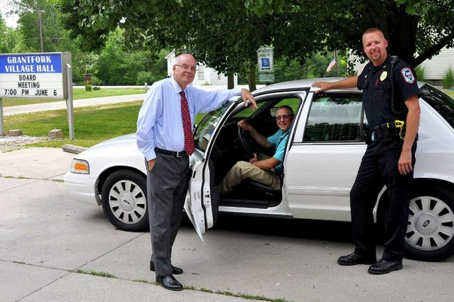 Madison County Chairman Alan Dunstan, left, presents Grantfork Mayor Steve Brendel, center, and Chief of Police Justin Rottman with a surplus county vehicle. The village will use the car as a backup police vehicle.