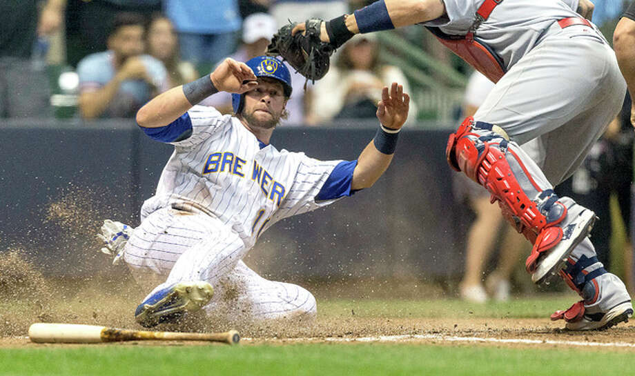 The Brewers' Kirk Nieuwenhuis, left, slides in safely past the tag of Cardinals catcher Yadier Molina on teammate Jonathan Villar's walkoff single to left in the ninth Friday in Milwaukee. Photo: Tom Lynn | AP Photo