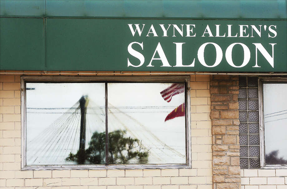 The Clark Bridge is reflected in the window of the former Wayne Allen's Saloon this week at the corner of East Broadway and Ridge Street. The closed bar will be re-opened later this summer as a Ruby's.