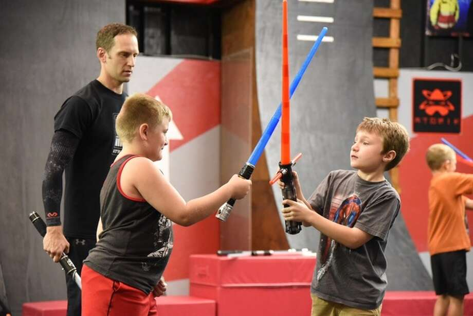 Shinobi Fitness owner and instructor Tim Minnick guides youngsters through light saber training Saturday. Minnick used the Star Wars twist to make the exercise more fun for children.