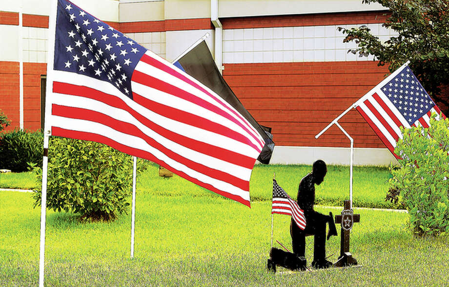 A silhouette cutout of a kneeling police officer, and additional flags, have been placed on the lawn of the Donald E. Sandidge Alton Law Enforcement Center in honor of the five officers slain in Dallas last week.