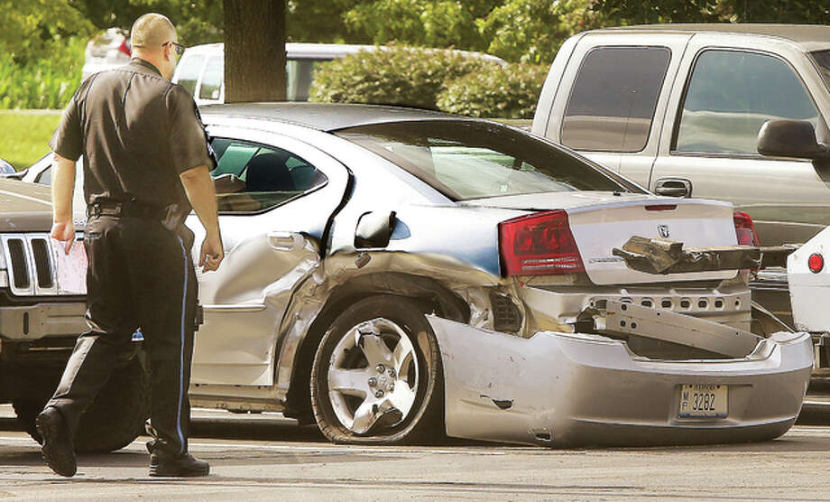 Alton Police Sgt. Mark Dorsey gets a look at a badly smashed detective car, a Dodge Charger, Tuesday at the city garage. A driver struck the car in front of the Donald E. Sandidge Alton Law Enforcement Center Friday evening. That driver of the car that struck the detective was charged with aggravated DUI and aggravated battery to a police officer, both felonies.
