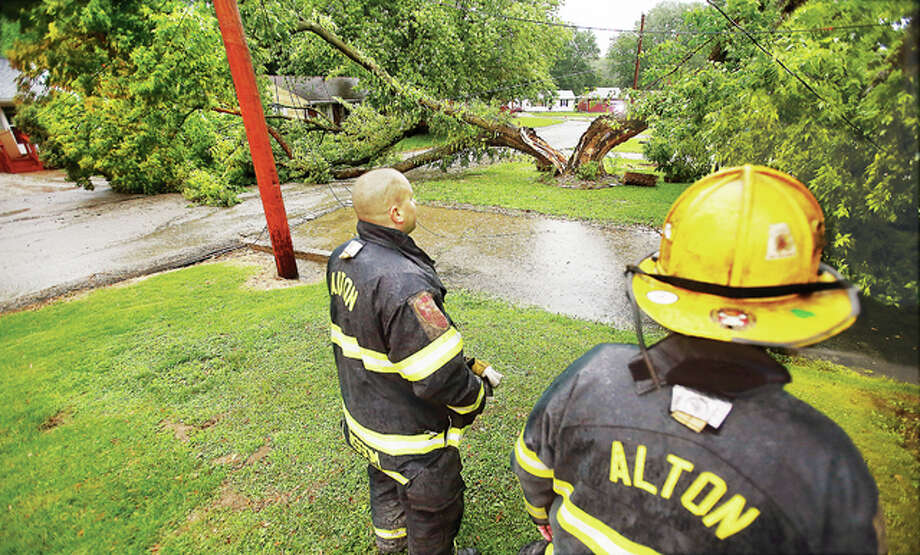 Alton firefighters stand by with a large tree that split Wednesday in the front yard of a house in the 3800 block of Western Avenue in Alton, knocking down cable and telephone lines, blocking the road and striking a small house. It was unclear if the house sustained any significant damage from the tree. A storm with strong winds blew through the area about rush hour Wednesday but caused only spotty damage locally. A smaller tree fell across College Avenue near Rock Spring Park causing Alton Police to close that roadway until the city's Forestry Department could arrive to cut it up.