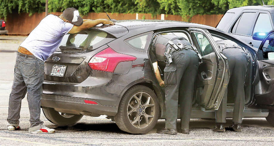 In a nearly hour-long search of a Ford Focus with two occupants Thursday, on the parking lot of the Shop 'n Save Fuel Express in Alton, the passenger, who was taken away by Alton detectives but not charged, according to police, lays on the car, trying to keep his hands out as instructed by police. Police searched the entire vehicle, including under the spare tire and the hood. The driver was handcuffed and taken into custody. Police apparently found what appeared to be drug paraphernalia and eventually towed the vehicle away. A run of the vin on the car indicated it was registered in California and reported to be re-possessed, according to police radio traffic, even though it had Missouri license plates on it.