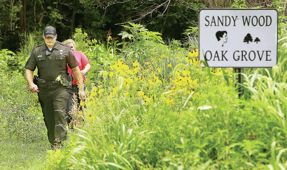An Alton police officer completes his estimated 600-yard hike out of the prairie and woods on the east side of the northern portion of Gordon More Park Friday after confirming that an abandoned full-size Dodge Ram pickup truck in the tree-line was indeed stolen. The vehicle was discovered by employees of the Alton Park and Recreation Department who reported it to police. The owner was going to try and drive the vehicle, which was stolen from a business in the 2600 block of East Broadway in Alton, back out of the woods and prairie.