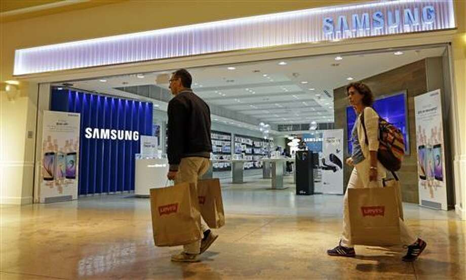 In this photo taken Tuesday, Feb. 9, 2016, shoppers walk by a Samsung store in Miami. On Friday, July 15, 2016, the Commerce Department releases U.S. retail sales data for June.