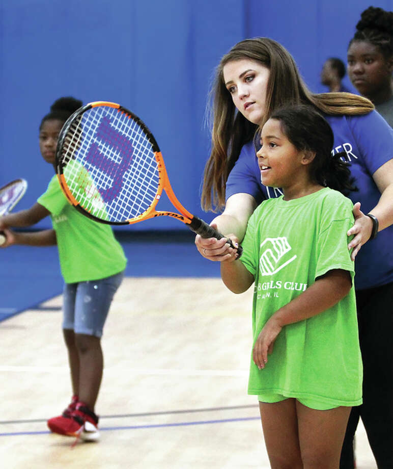 LCCC tennis player Anna Ballard helps Tianna Taylor learn to use a tennis racquet during a children's tennis clinic held in the George C. Terry Riverbend Arena on Saturday. More than 40 children from the community and the Alton and Bethalto Boys and Girls Clubs attended the clinic where they learned and practiced how to play tennis. Photo: LCCC Athletics