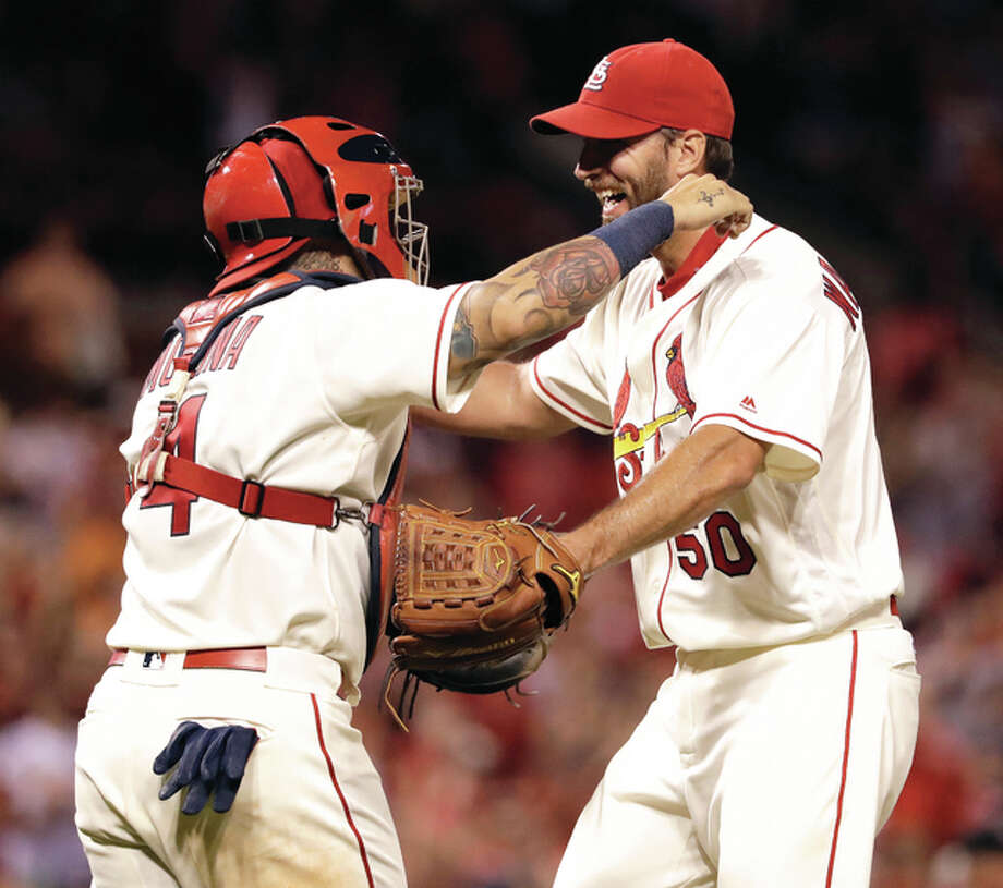 Cardinals pitcher Adam Wainwright (right) gets a hug from catcher Yadier Molina after throwing a complete-game shutout against the Miami Marlins on Saturday night a Busch Stadium. Photo: Associated Press