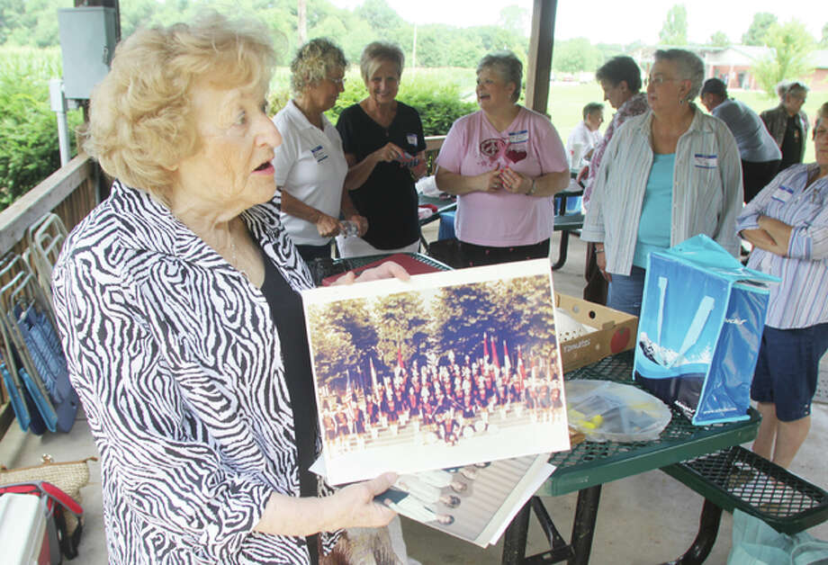 Norma Helwig Glazebrook, director of the Piasa Indians, a local drill team that was active from 1950 through the mid-1970s, shows off a photograph of one of the groups during a recent reunion at Robert E. Glazebrook Community Park, named for Glazebrook's late husband and located at 1401 Stamper Lane in Godfrey.
