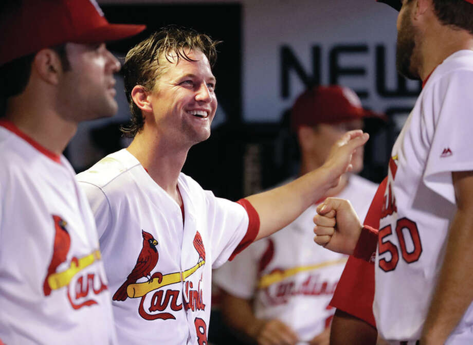Cardinals pitcher Mike Leake (center) smiles as he talks with teammate Adam Wainwright (50) after the sixth inning against the San Diego Padres on Monday night at Busch Stadium. At left is the Cardinals' Jaime Garcia. Leake struck out 11 and walked no one in six inning for the win. Photo: Associated Press