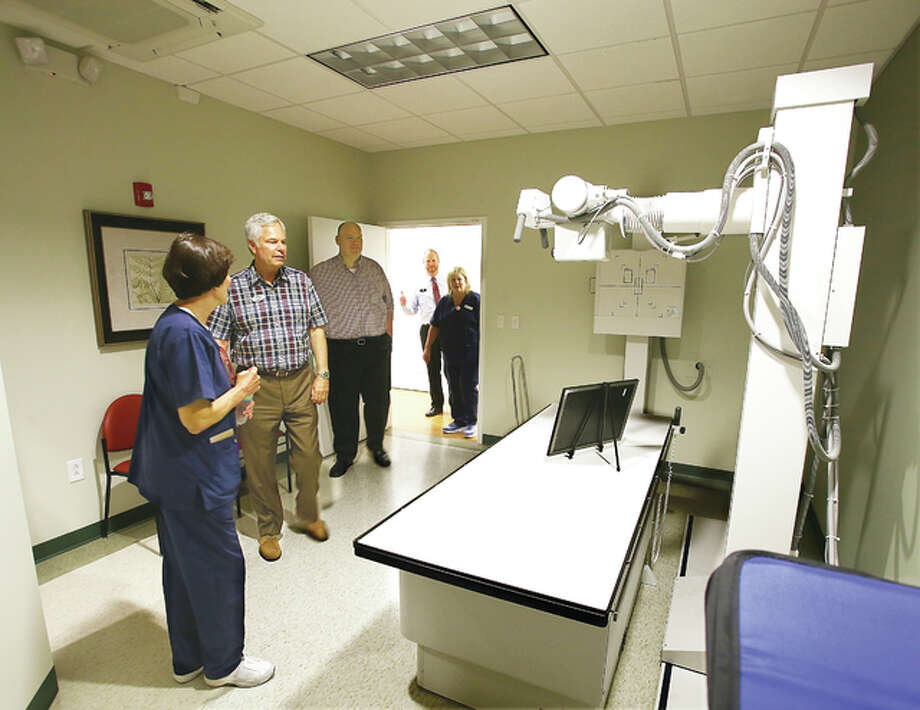 The Stevenson family, including owner Dave Stevenson, left, of Quality Cadillac, Buick, GMC, which is located nearby, get one of the first tours of the new MedExpress urgent care facility that opened Tuesday on the Homer Adams Parkway in Alton. Nurse Gail Stotler, BSN,RN, left, shows off the facilities X-ray room. MedExpress can handle a variety of medical issues like colds, broken bones, stitches, X-rays and more. Photo: John Badman | The Telegraph