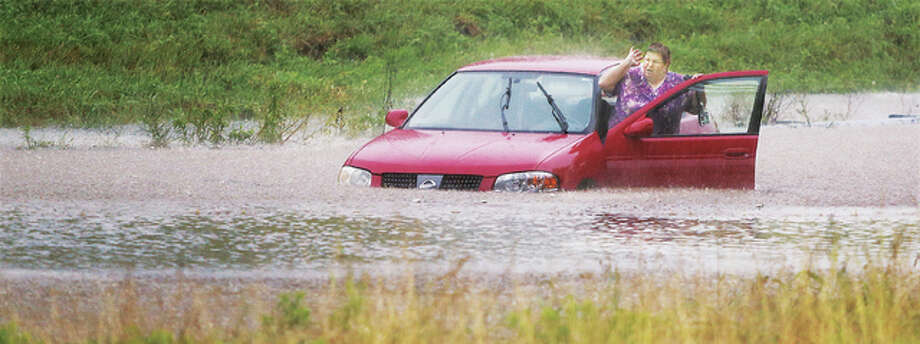 A woman who found herself — and her car — in deep water in the 4700 block of Wanda Road in Roxana Wednesday strains to hear what firefighters are shouting at her. Roxana firefighters and police were already on the scene because another motorist had driven into the exact same waters and also stalled out. The woman was uninjured, but escorted out of the high water that overwhelmed her Nissan. The scene was repeated all over the area Wednesday morning as heavy rains caused flash flooding, closing roads and stranding motorists across the area. Several houses in Bethalto suffered major water damage as creeks became powerful raging rivers.
