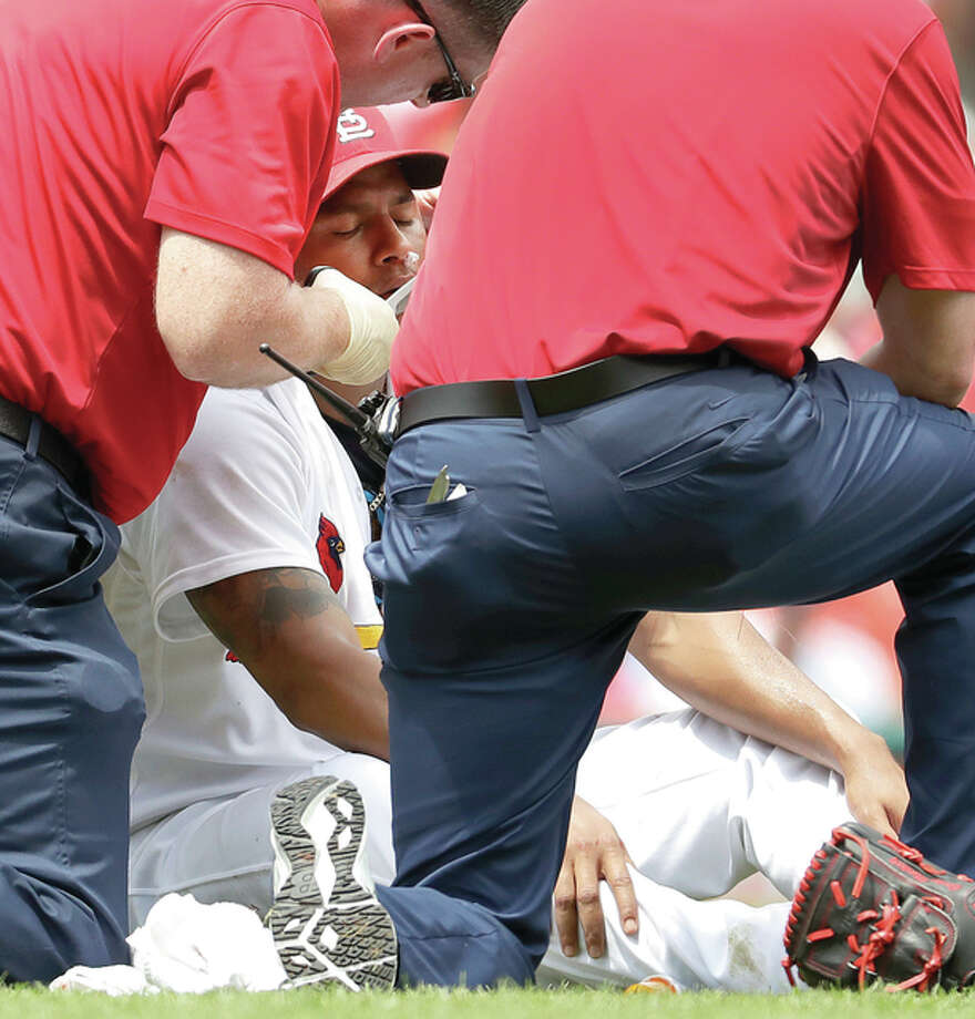 Cardinals starting pitcher Carlos Martinez is tended to by trainers after getting a nose bleed in the second inning of the first game of a doubleheader against the San Diego Padres Wednesday in St. Louis. Martinez was able to stay in the game. Photo: Jeff Roberson | AP Photo