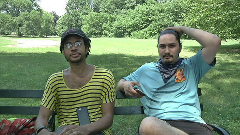"In this July 13 frame grab from video, Jordan Clark, left, and Lewis Gutierrez sit in Prospect Park as they talk about their new ""Pokemon Go"" business in the Brooklyn borough of New York. They are among the new entrepreneurs who offer their services as ""trainers"" for the game at $20 per hour - logging onto a client's ""Pokemon Go"" account and effectively running up their score while a client is stuck at work or sitting in class."