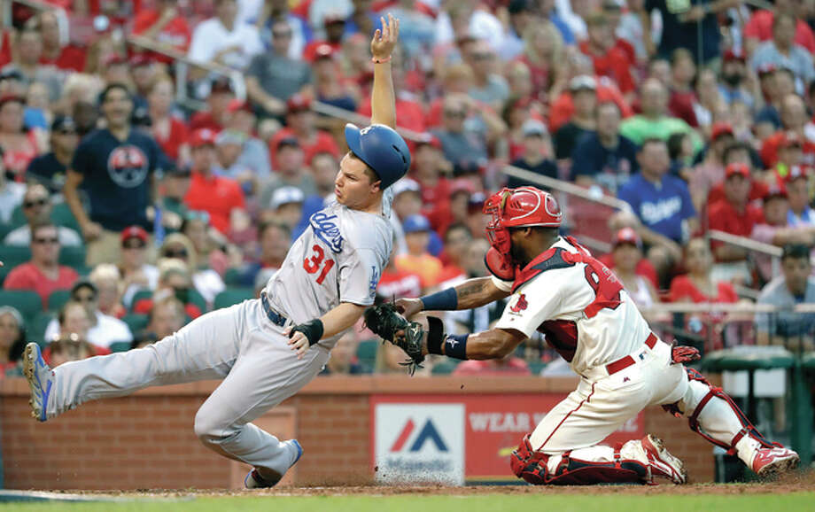 The Dodgers' Joc Pederson, left, is tagged out at home by Cardinals catcher Alberto Rosario in the sixth inning Saturday night in St. Louis. Photo: Jeff Roberson) | AP Photo