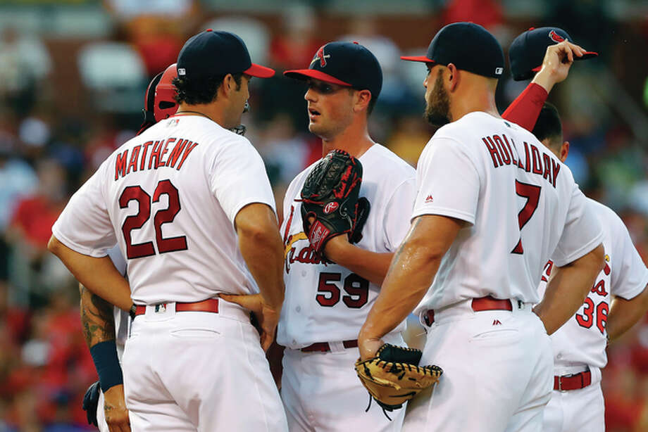 Cardinals manager Mike Matheny (left) pays a visit to the mound to talk with starting pitcher Mike Mayers (center) during the first inning against the Los Angeles Dodgers on Sunday night at Busch Stadium. Mayers, making his first big-league start, took the loss. Photo: Billy Hurst / Associated Press