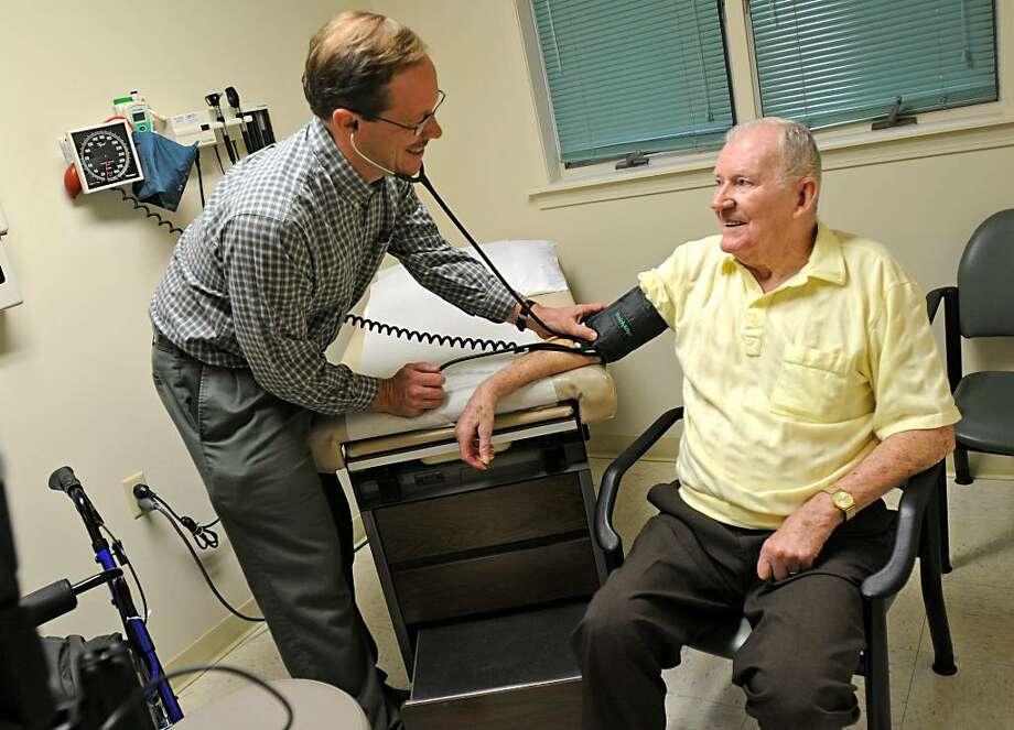Dr. Michael Adams examines Malcolm Rounds, 86, of Queensbury, at the Moreau Health Center in South Glens Falls. (Lori Van Buren / Times Union) Photo: LORI VAN BUREN