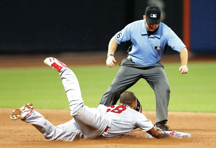 Second base umpire Mike Muchlinski watches as the Cardinals' Alberto Rosario slides safely into second on a third-inning double in the second game of Tuesday's doubleheader against the Mets in New York. Photo: Kathy Willens | AP Photo