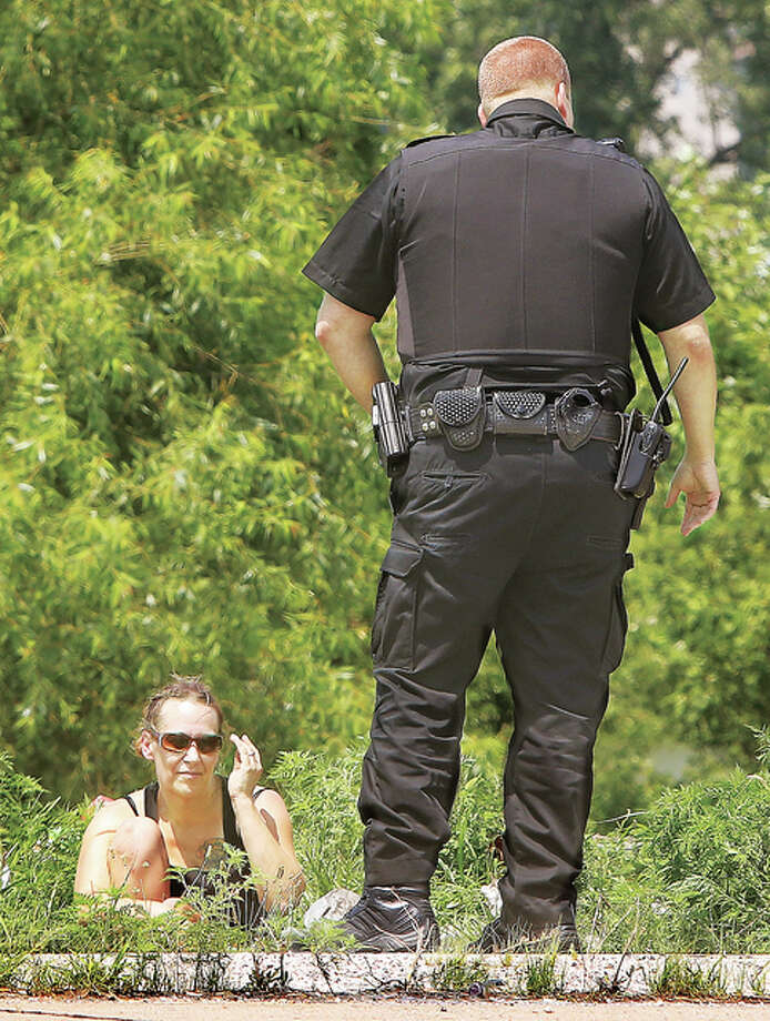 An Alton Police officer stands over a woman described as a family member of homicide victim Christopher Aaron Gernigin as she sits alone Wednesday in the grass where his body was found, just off the northbound lanes of the Clark Bridge in West Alton, Missouri. The victim was found late Friday night. The woman and another woman were looking around the area where the Alton area man's body was found. The Missouri State Highway Patrol has not been releasing information about the case.