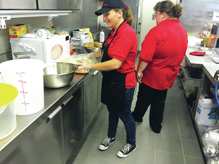 A Quick Bite employee Angel Wagner prepares a fresh salad as Manager Lisa Sumpter observes. The cafeteria opened in the Madison County administration building and employees disabled individuals through non-profit organization Challenge Unlimited.