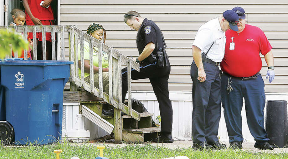 An Alton Police officer speaks with a despondent woman who was in a mobile home Friday with at least nine children in the 100 block of Tara Ct. in Alton. After investing the death of an 8-month-old infant there, police said the tragic death was accidental.