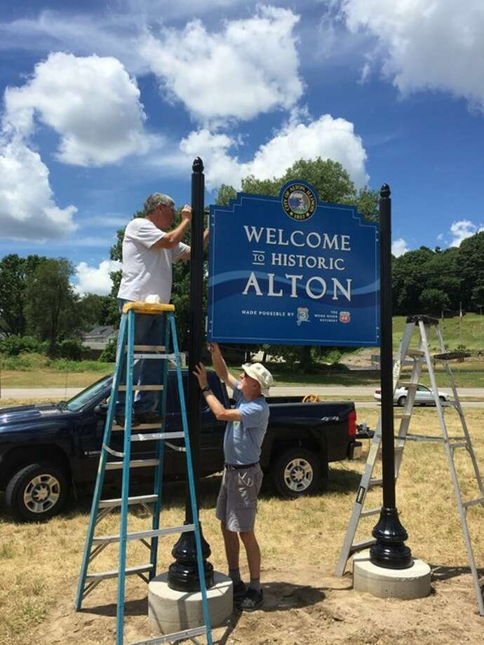 Alderman David Boulds, 7th Ward, stands on a ladder as he and Altonian Jim Hanlon secure the new welcome sign in place on a post north of East Broadway, just inside the border with East Alton. The sign is Hanlon's son Ryan's project. Submitted art.
