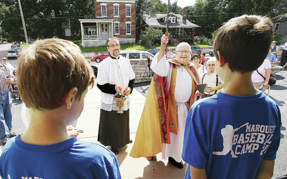 The Holy Water was flying Friday afternoon as Rev. Albert Allen, right, blessed Alton's Ss. Peter and Paul Catholic School on State Street following major repairs from foundation subsidence. Students, who spent part of the year in the Alton School District's former Mark Twain School, will return to classes this fall in their old building.