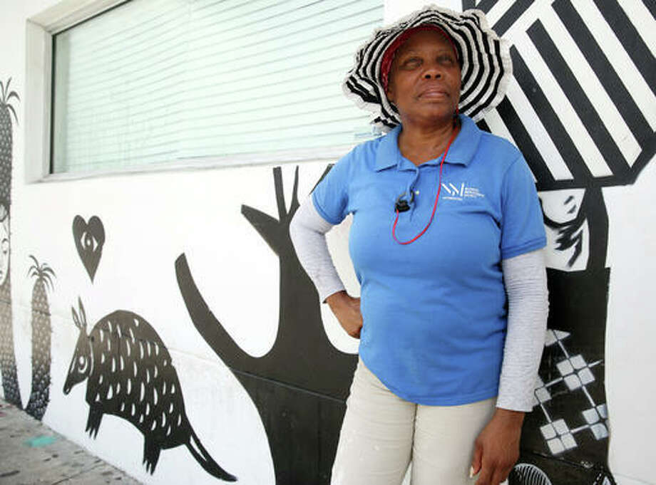 Glendina Rosebo, 54, of Miami, takes a break from cleaning the sidewalks in the Wynwood area of Miami, Friday, July 29, 2016. Florida health officials said that four patients in Florida infected with the Zika virus were infected in the Wynwood area. These cases are believed to have caught the virus locally through mosquito bites. Rosebo has seen Miami-Dade mosquito control personnel spraying in the area the last few days. (AP Photo/Marta Lavandier)