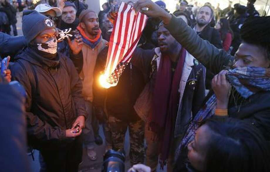 """In this Feb. 23, 2016 file photo, protesters burn an American flag in Chicago. Champaign County Ill., State's Attorney Julia Rietz was alerted on July 4, that police had just arrested a resident on suspicion of burning an American flag. Rietz said she knew """"immediately"""" that the Urbana Police Department needed to release him. The state law used to jail him, though clear in its prohibition of desecrating either the U.S. or state flags, is unconstitutional."""