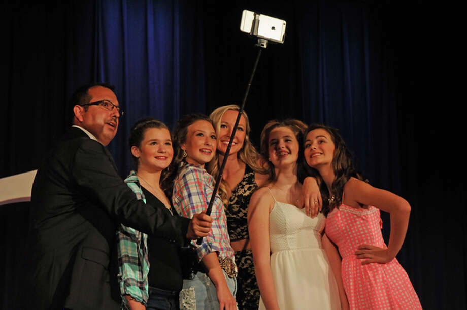 "Emcees Phil McDowell and Anne Marie Connelly take a ""selfie"" with Junior Miss contestants on stage during the 2016 Miss Madison County Fair Queen and Junior Miss Pageant held on Saturday in Highland."