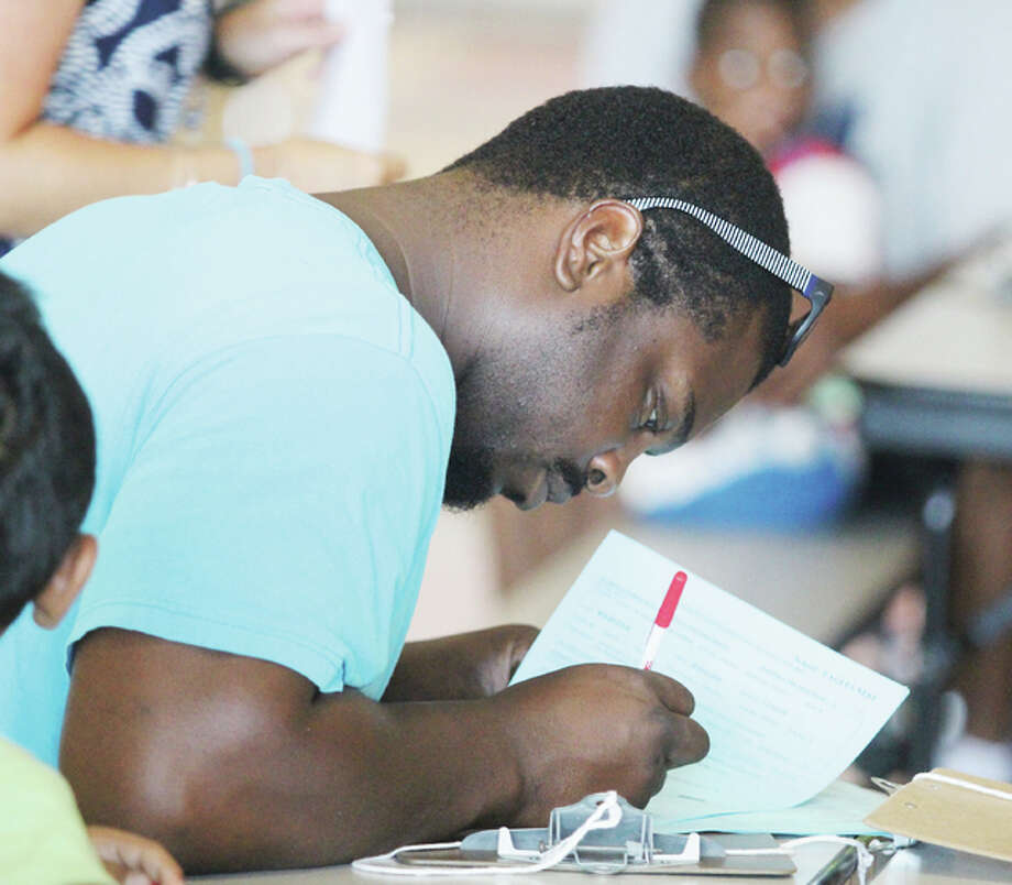 Jermaine Webster fills out paperwork for three of his four children during registration for elementary and junior high school, held at Alton High School Tuesday through Thursday. District officials said they saw good crowds at the three-day event. High school registration will begin Monday, Aug. 1 at AHS.