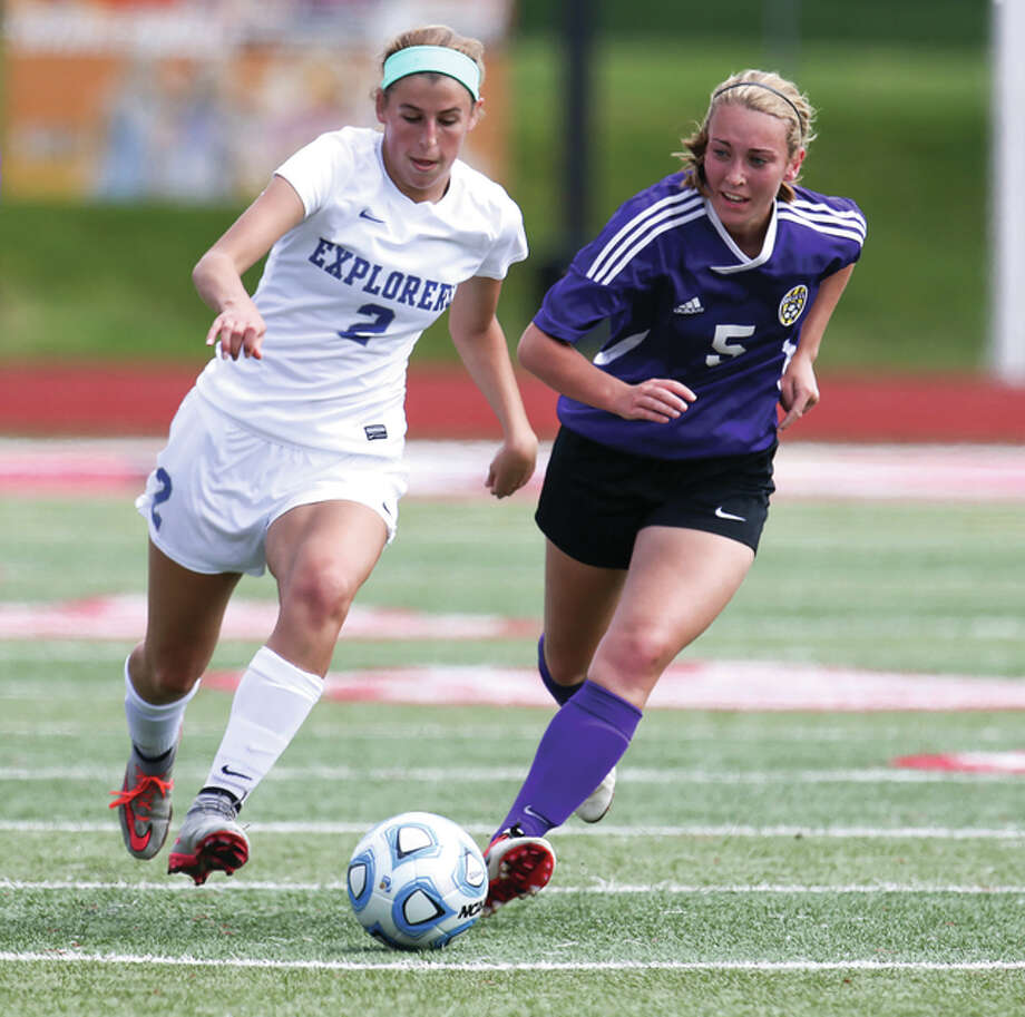 Marquette Catholic's Annabelle Copeland (left) moves the ball up the pitch against Williamsville's Annie Gantt during the Class 1A state girls soccer third-place game Saturday at North Central College in Naperville. Photo: Sean King / For The Telegraph